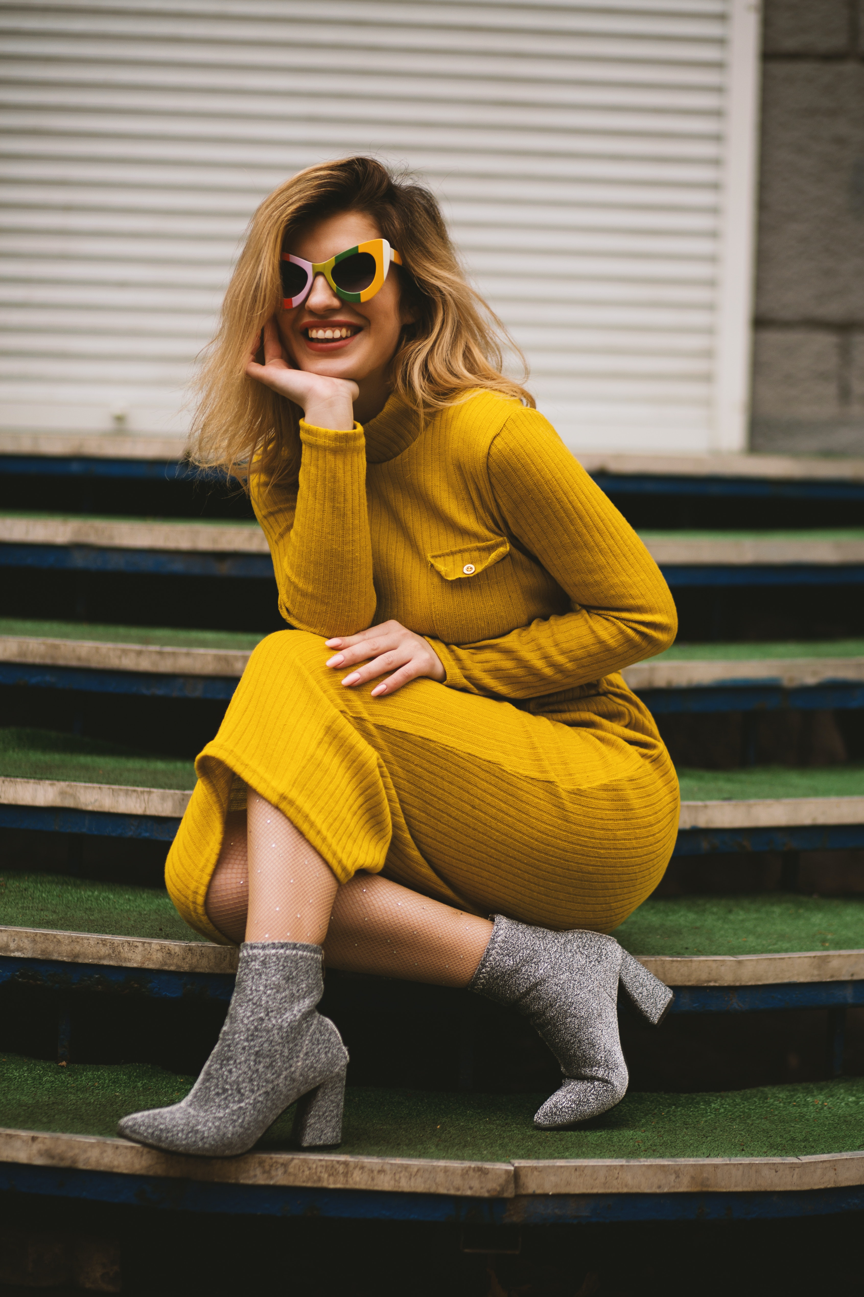 Stylish model in a yellow dress and sunglasses posing on the steps.