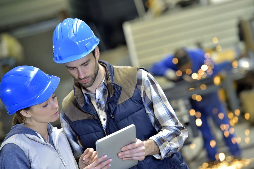 manufacturing workers in factory looking at digital tablet