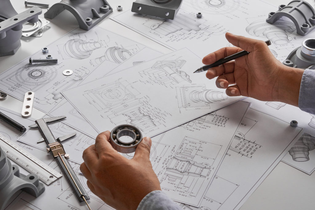 product development consultant designing product with engineering blueprints on table