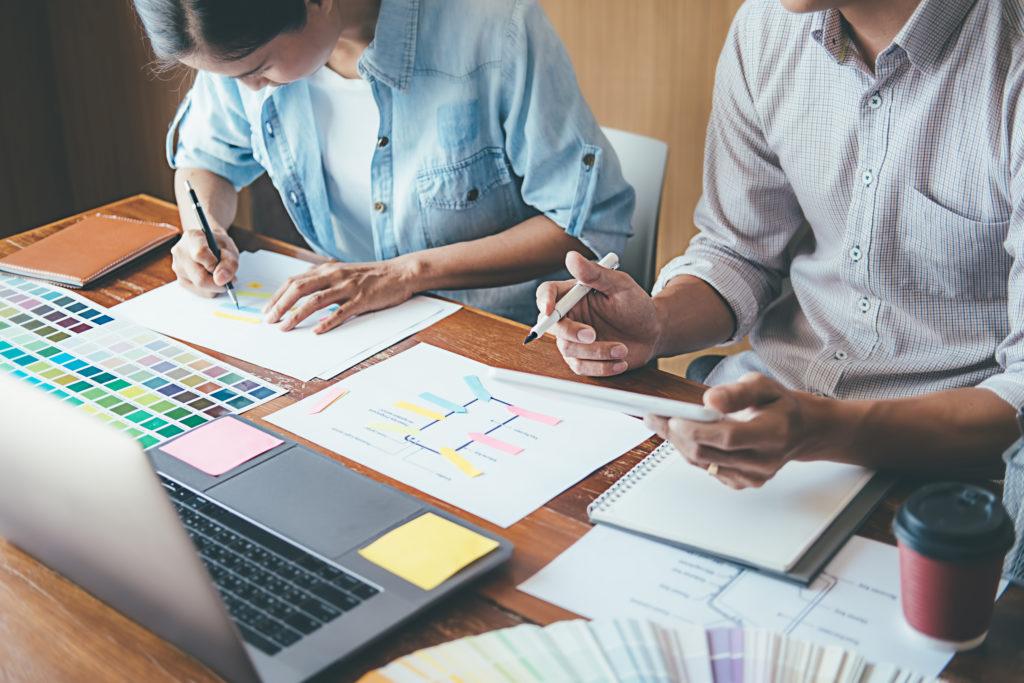 designer planning development with coworker at desk