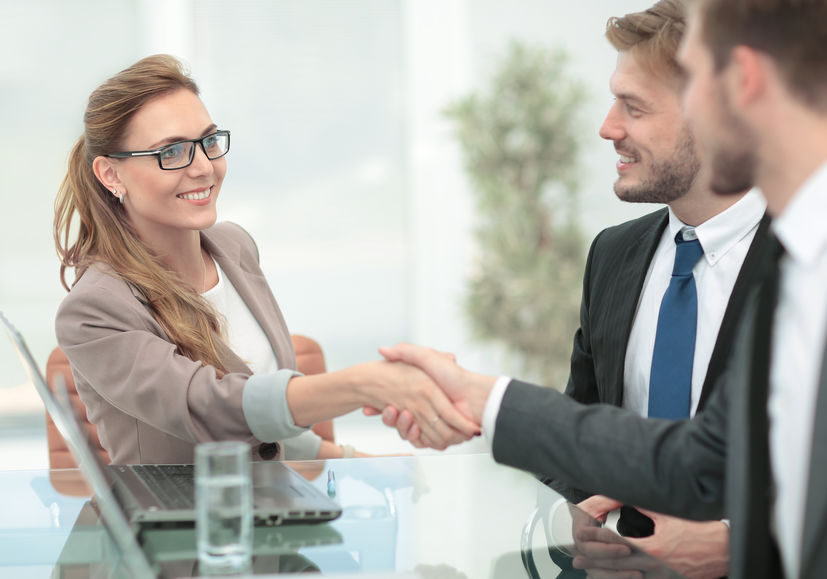 Young businesswoman shaking hands with young businessmen