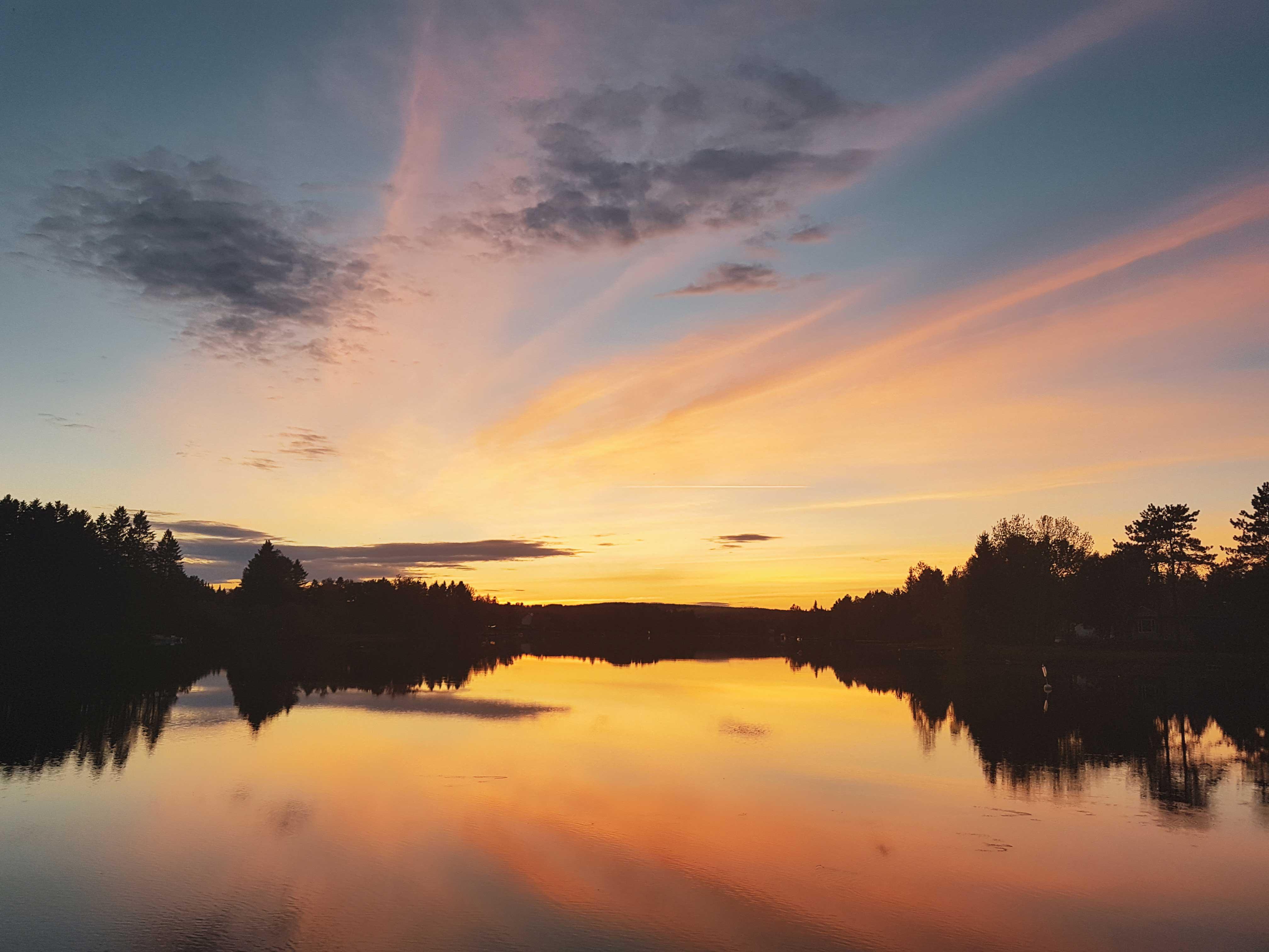 Un coucher de soleil sur une rivière. Le ciel est bleu, rose, et jaune. La rivière reflète les couleurs.