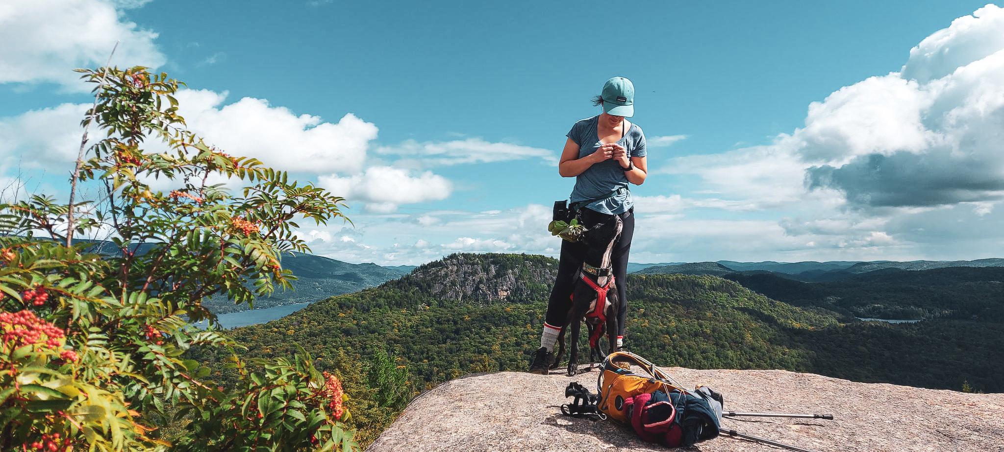 Au sommet de la montagne, sur un cap rocheux, Enzo se trouve entre les jambes d'Audrée et regarde vers le haut. Audrée regarde aussi Enzo. Au loin se trouvent d'autres montagnes et une rivière.