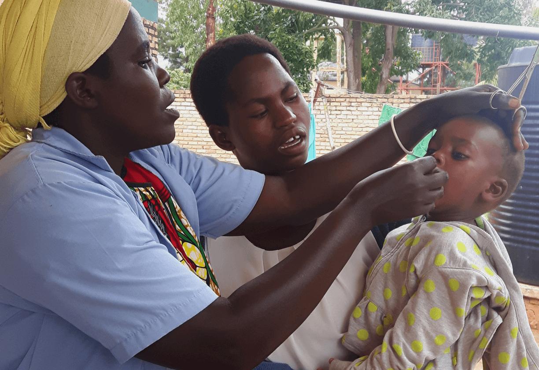 Nurse giving medicine to toddler