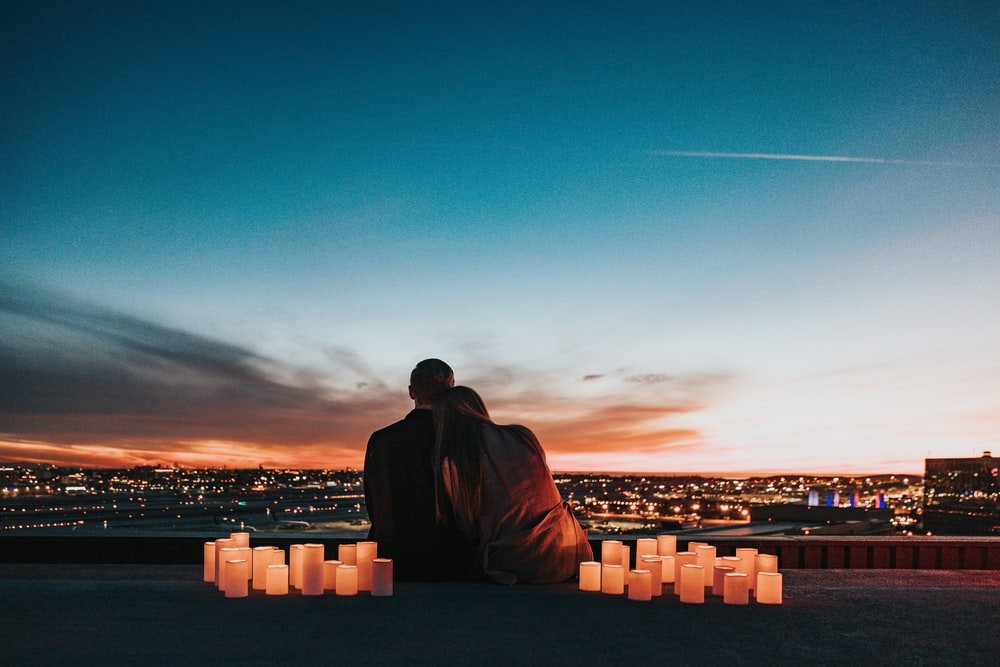 couple sitting on the field facing the city
