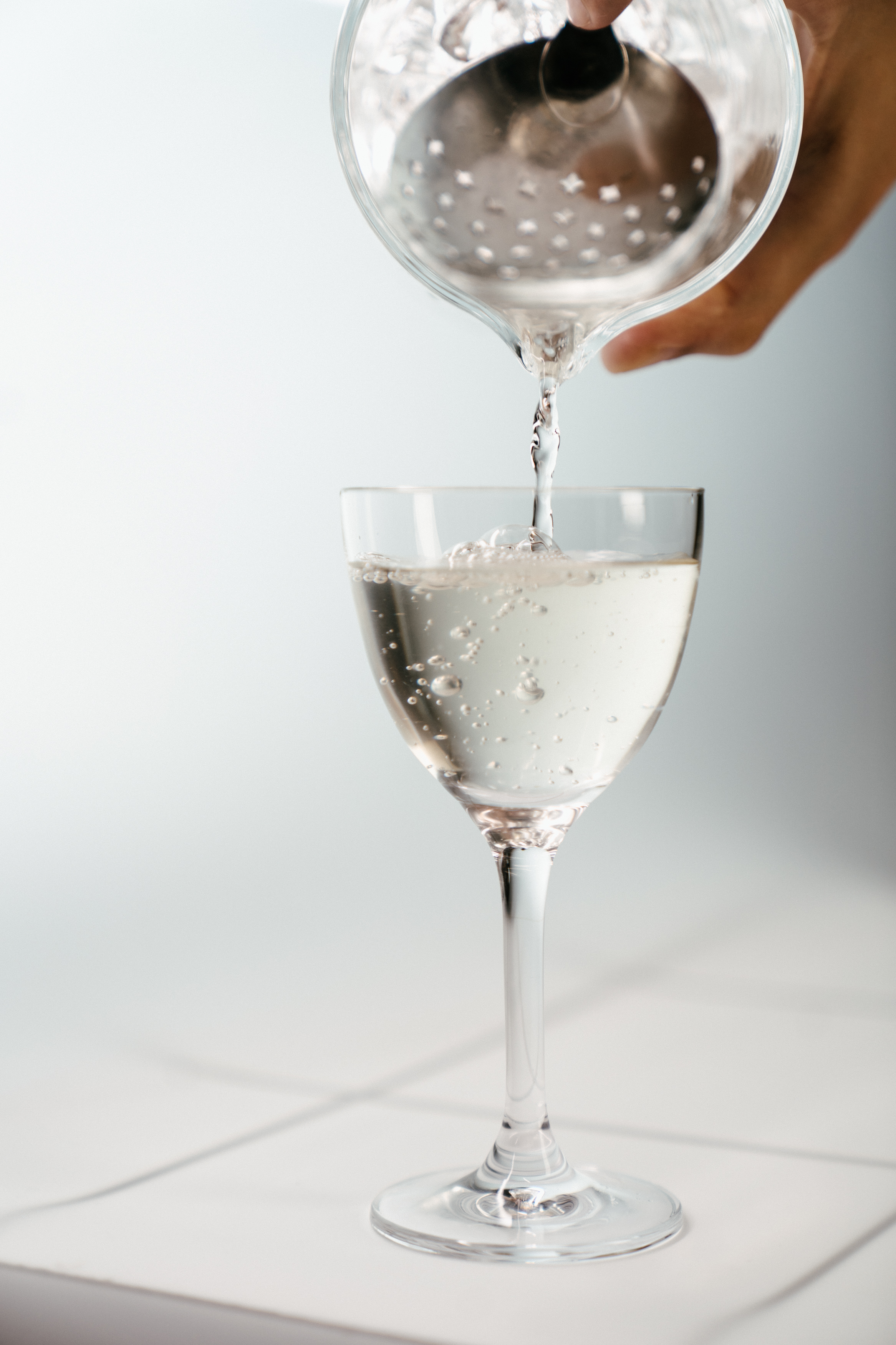 Person Pouring Water on Clear Wine Glass