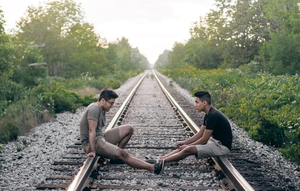 2 person sitting on train rails during daytime