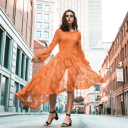 A woman in orange dress posing for camera