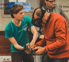 Fontys Pulsed Embrace student helping older man with a Virtual Reality experience
