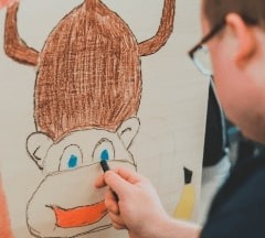 A boy drawing a figure on a wooden panel during the minor demo day