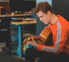 Fontys Pulsed student with a bright shirt playing guitar
