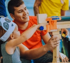 A Fontys Pulsed student showing a young boy his custom made water-gun