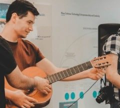 A Fontys Pulsed student showing how to play guitar to others