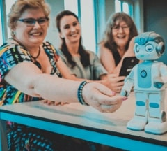 Three people looking happy at a small robot during the minor demo day