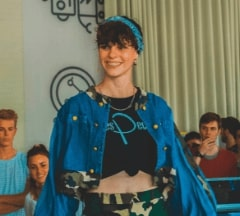 A Fontys Pulsed student standing tall while walking over a catwalk during a demo