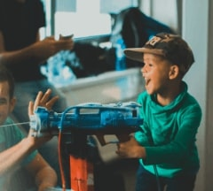 A young boy looking thrilled while shooting his water-gun during the minor demo day
