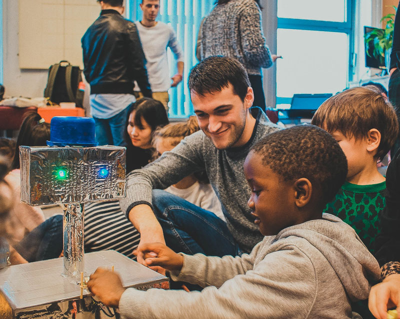 An Embrace student showing his shitty robot to a kid