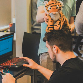 A Fontys Pulsed student programming a prototype of a type of hardware with a tiger plushy on his head