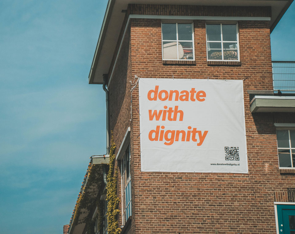 Pulsed students hang up a promotional banner for the Donate With Dignity challenge that aims to help Lebanon