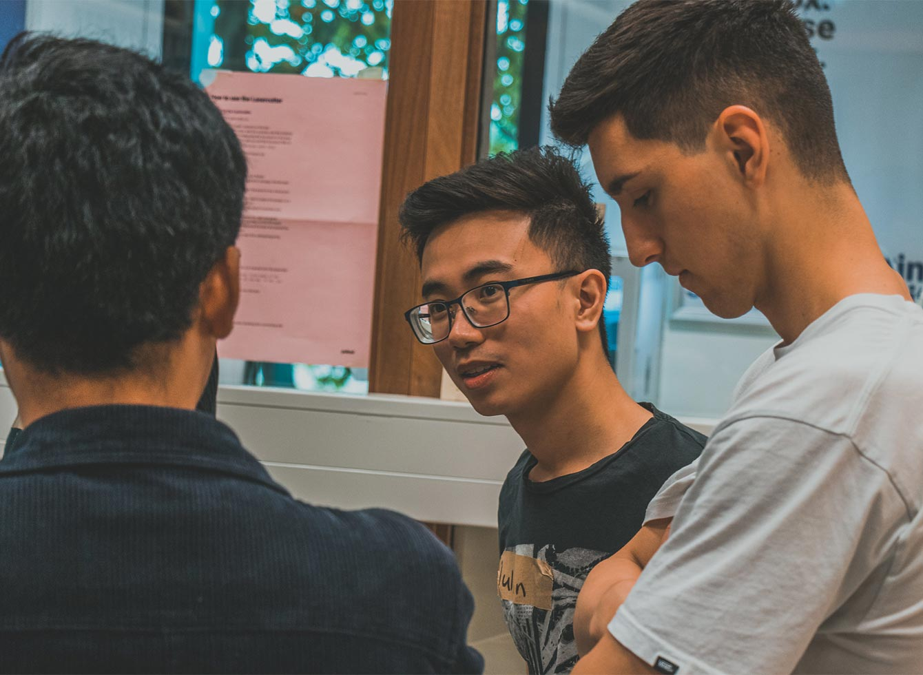 Three young men discussing how to work on their prototype in the Master Program Digital Technology Engineering