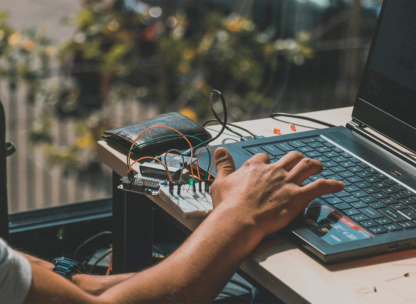 A hand reaching for the computer in the Master Program Digital Technology Engineering