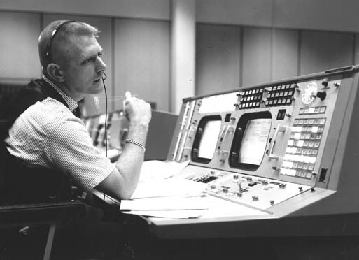 Image of Eugene F. Kranz sitting at desk wearing headset in Mission Control.