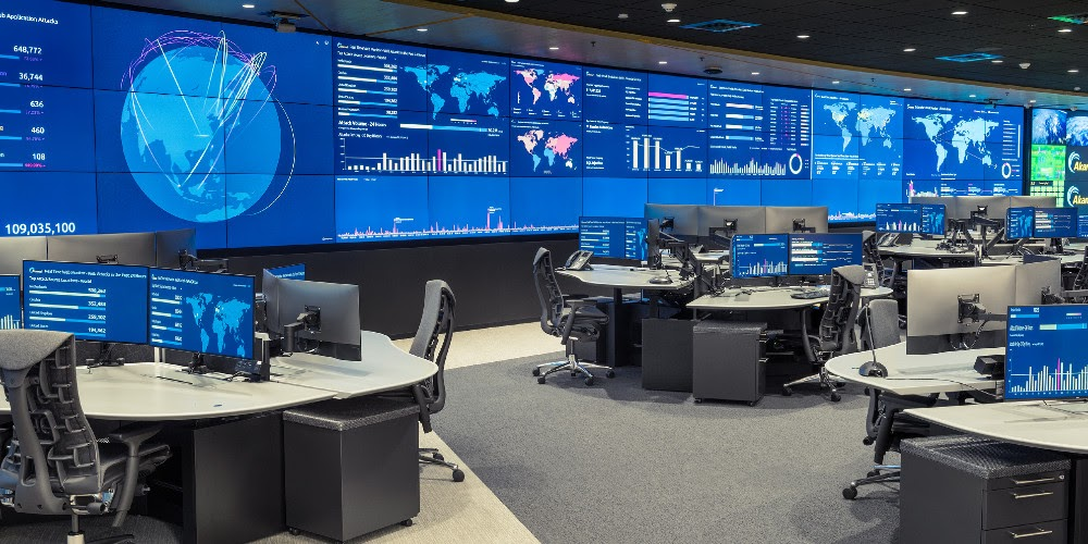 A modern Mission Control room with walls of screens showing graphs, charts, and maps.