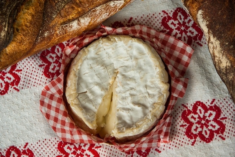 A close-up of Camembert before adding fresh garlic and thyme topping, with crispy Baguette.