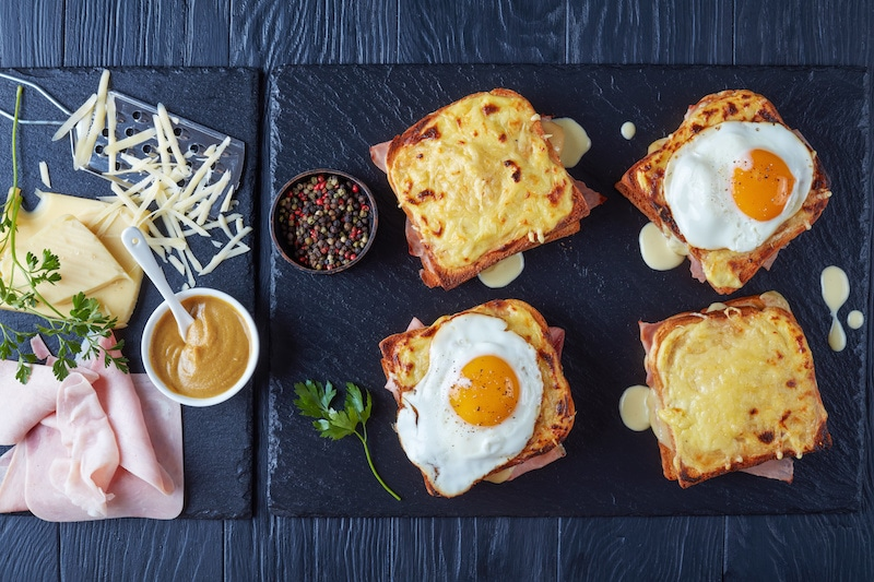 Four Croque-Monsieur and Croque-Madame on a thin granite board.