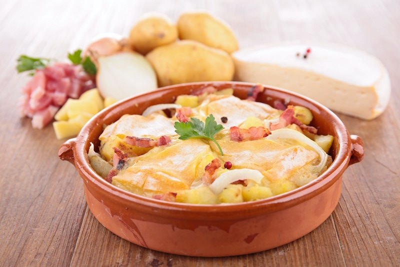 Tartiflette Savoyarde served in a traditional cookware terracotta bowl, with Reblochon cheese in the background.