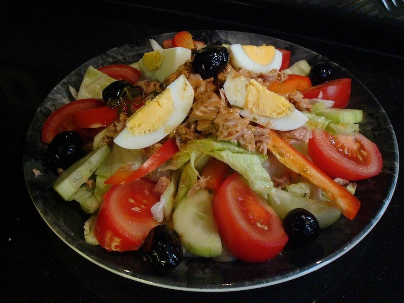 A close up of Salade Niçoise with sliced tuna, tomatoes, cucumber, hard-boiled eggs and olives served on a plate.