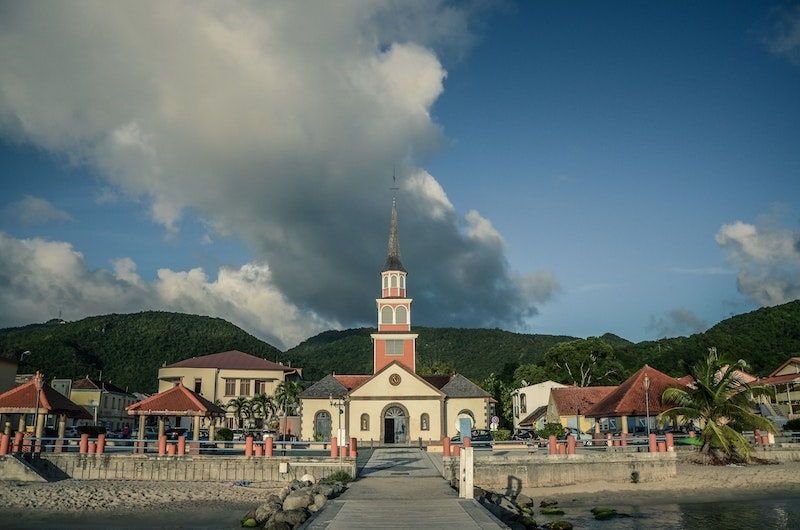 View of the Saint-Henri Church and its red tower, bordering the beach.