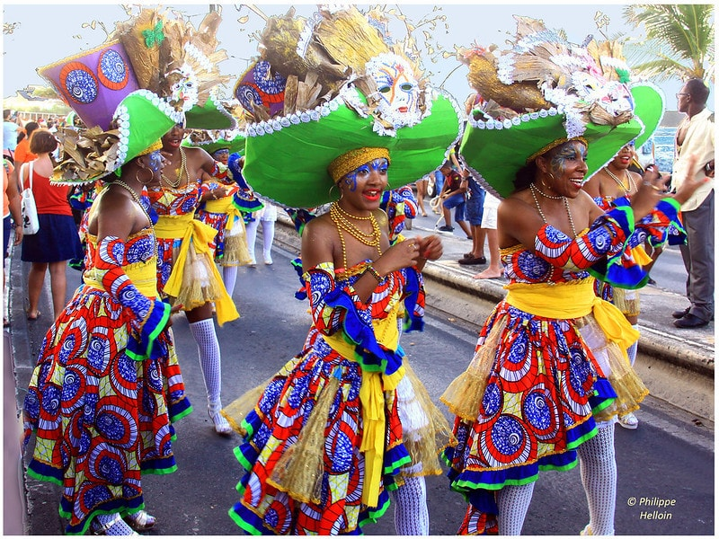Three dancers are parading and wearing colourful outfits with large green hats during the Carnaval in Basse-Terre in the street.