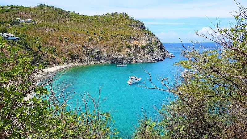 View of a gorgeous bay with sandy beach and turquoise water, where three boats are floating.
