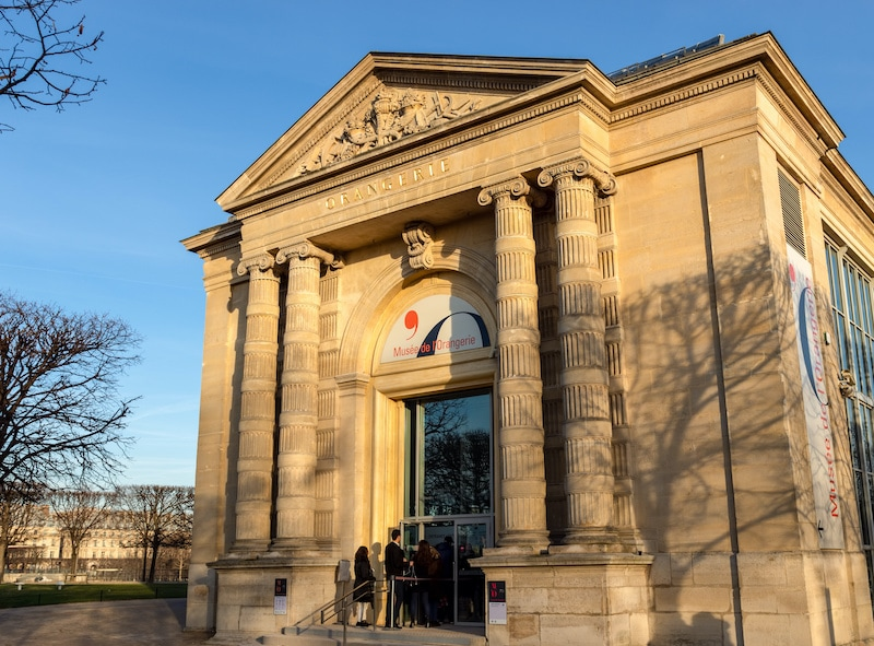 Day view of the Orangerie neoclassical-style entrance door with four columns and a pediment