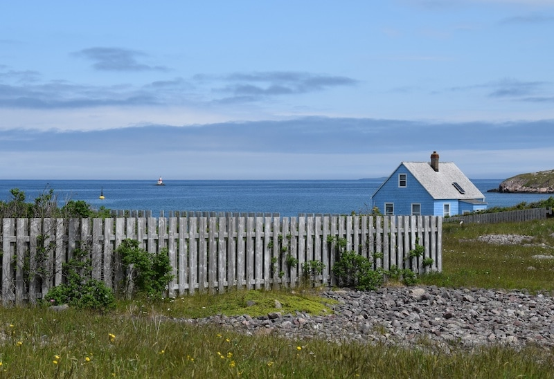 Wooden picket fence along the shoreline of Île-aux-Marins at Saint-Pierre and Miquelon. There is a blue heritage house on the right.