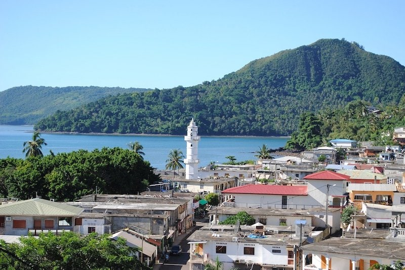 View of the white minaret of Sada and colourful roofs bordering the Indian Ocean, with a green hill in the background.