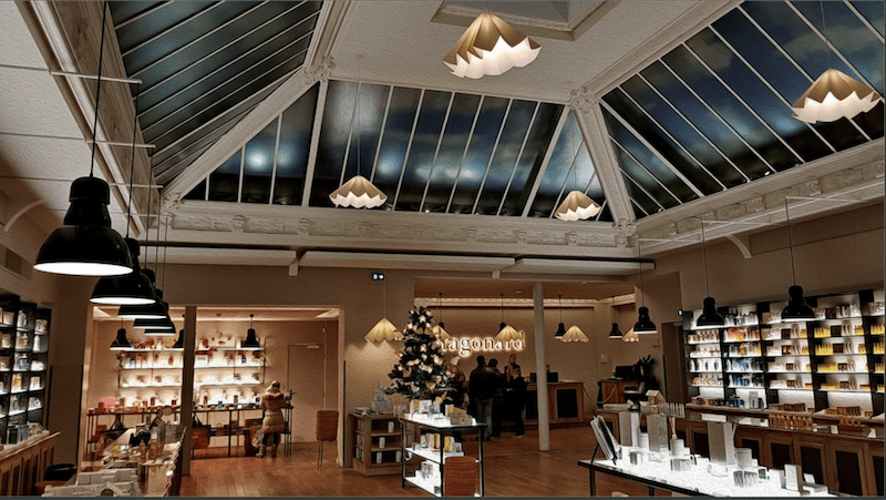 View of the shop of the museum and its glass roof. Shelves present the complete range of Maison Fragonard perfume products