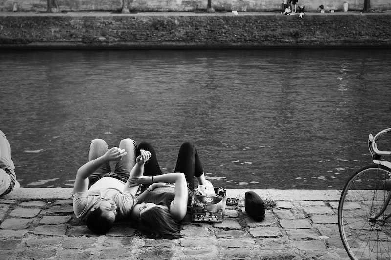 Black and white image of two lovers lying on the cobblestones along the banks of the Seine.