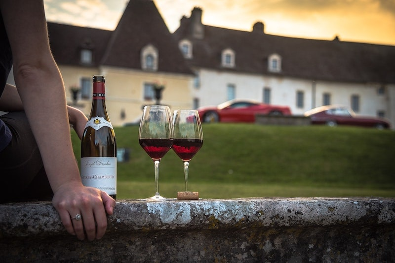 Chambertin wine bottle with two poured glasses into the setting sun in beautiful light captured in Burgundy's point-of-view perspective. Chambertin is the most important Grand cCru vineyard in Gevrey-Chambertin, one of Burgundy's northernmost wine villages.