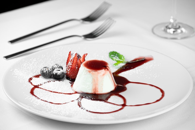 Pastry with raspberry coulis, surrounded by fresh strawberries and blueberries on a white plate decorated with sauce and mint.
