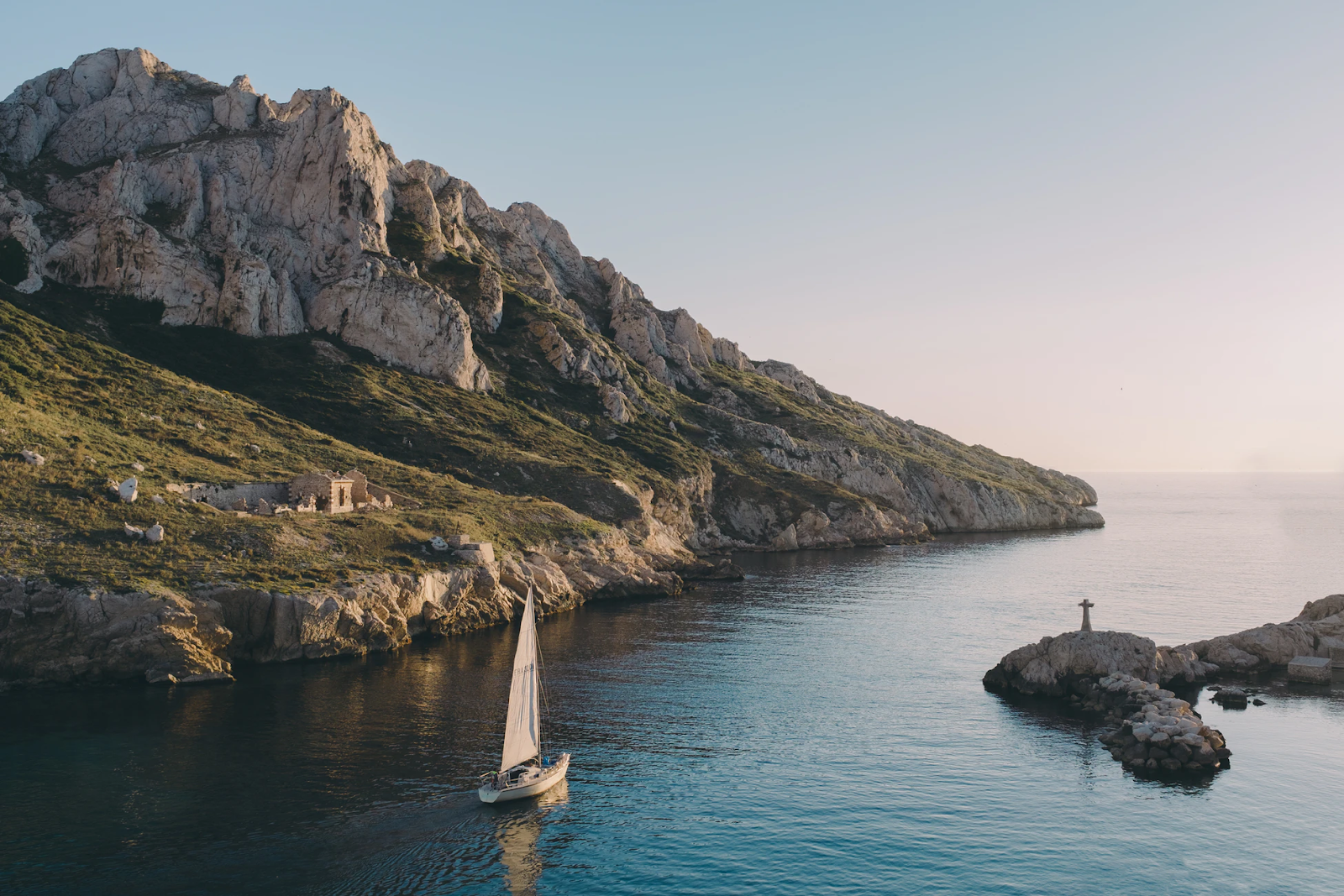 View of the Calanques at sunset time with a boat passing by