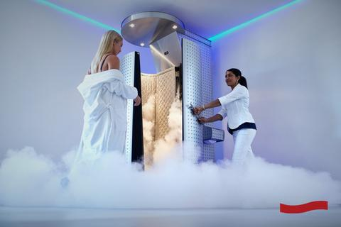 Blonde woman in a white robe going inside a cryotherapy chanmber