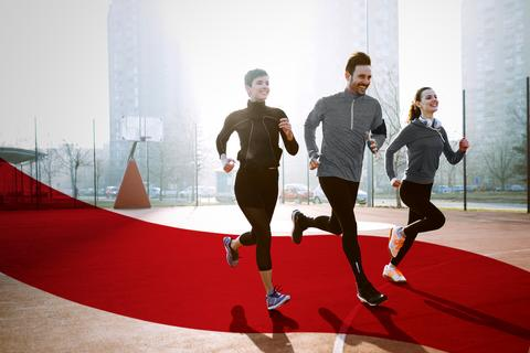 Two women and one man wearing running outfits, jogging in the city