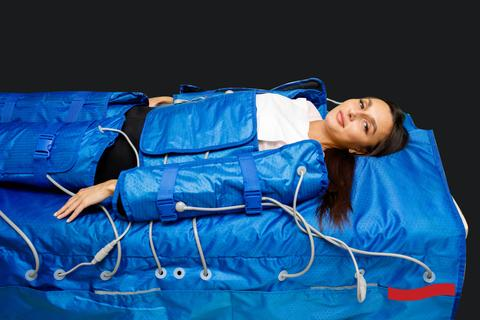 Woman wearing a blue full-body compression suit laying down on a bed