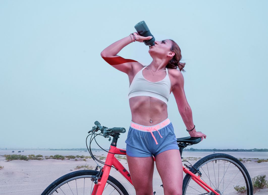 Woman Drinking Water While Standing Beside Her Bike