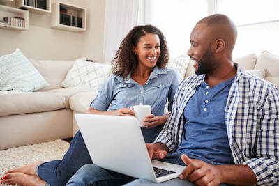 Step 2 of how it works for We Buy Any Home UK service. Couple discuss options while using laptop.