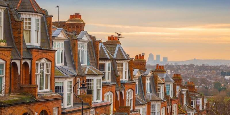 We Buy Any House main article image, a row of houses with a city and sunset in the background