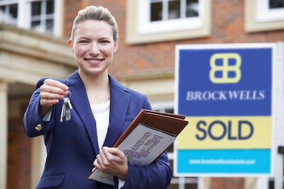 How It Works step 3. Estate agent smiling outside property after completion.
