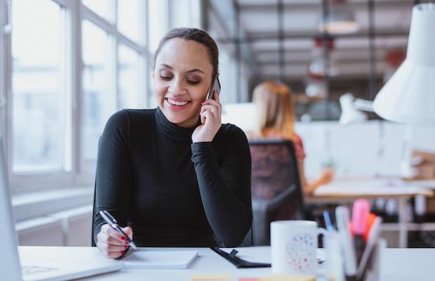 Arrange a consultation with us. Picture of a smiling lady on a phone call.